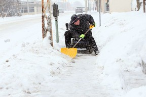 From the seat of his mobility scooter, Don Hamel clears snow from the Erie Street East sidewalk on Feb. 9, 2018.
