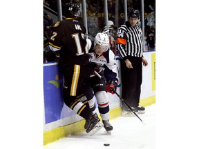Windsor Spitfires' Tyler Angle (7) hits Sarnia Sting's Jonathan Ang (12) in the first period of Friday's Game 5 in their OHL Western Conference quarter-final at Progressive Auto Sales Arena in Sarnia. (Mark Malone/Chatham Daily News/Postmedia Network)