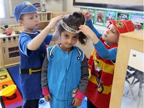 """Christ the King Catholic Elementary School JK/SK students Kevin, left, and Kenny help Laneta, centre, with her costume in an """"inquiry station"""" Thursday April 26, 2018.  The inquiry station is one of several new ways of learning."""