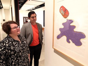 Art Gallery of Windsor curator of contemporary art Jaclyn Meloche, left, and Jose Daiz, chief curator at Pittsburgh's Andy Warhol Museum, view Warhol's 1985 depiction of New Coke during a May 31, 2018, unveiling of new exhibits.