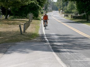 Cyclist Art Drake carefully rides along a portion of County Road 50 with no bike lane in Kingsville, Ontario on July 23, 2018.