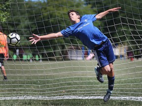 Aidan Belcastro, 13, tries to make a save in goal during a soccer camp at Green Acres Optimist Park in Tecumseh, ON. on Friday, July 6, 2018.