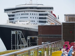 A woman relaxes on a patio near the docked luxury liner Queen Mary 2 in the Halifax Harbour on June 13, 2017.