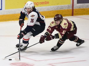 Windsor Spitfires assistant captain Chris Playfair skates the puck out of his own end with Peterborough Petes assistant Adam Timleck chasing his down in OHL action at the Memorial Centre on Saturday, Oct. 13.