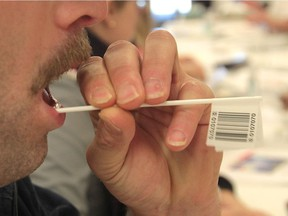A volunteer provides a DNA sample in 2013 for the OneMatch Stem Cell and Marrow Network at a University of Windsor event hosted by the Katelyn Bedard Bone Marrow Association.