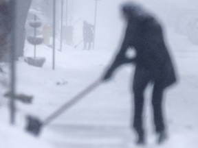 Two people clear snow from the sidewalks on Hall Avenue as a snowstorm blankets the region on Jan. 28, 2019.