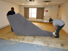 ALPHA House in Forest Glade is being restored as a community asset through a unique partnership between private investors, local non-profit organizations, and support from community members. The building was purchased by private investors, will become the new home of Matthew House Refugee Centre. In photo, Babatunde Lawal, left, and Khaled Omar remove old carpet from the former A.L.P.H.A. House.