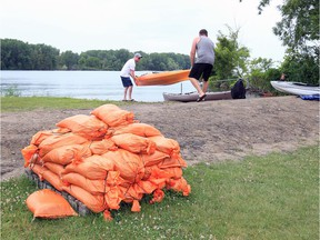 A skid of sandbags are ready for use at Shanfield Park Shores Park in East Riverside Tuesday. In photo, kayakers prepare to launch for a paddle to Peche Island.