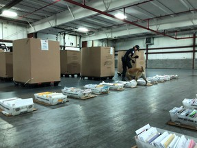A U.S. Customs and Border Protection canine team checks a mail shipment from Canada. The agency said more than 170 shipments of small amounts of illegal drugs were seized this month from Canadian mail trucks crossing into Michigan over the Blue Water Bridge.