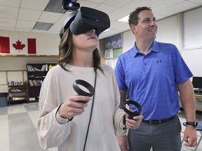 Julie Daragon a teacher with the Windsor Essex Catholic District School Board and Doug Sadler, principal of information technology, test out virtual reality equipment at St. Michael's Adult Secondary School in Windsor, ON. on Wednesday, August 28, 2019.