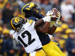 Nico Collins of the Michigan Wolverines makes a first quarter catch against D.J. Johnson of the Iowa Hawkeyes at Michigan Stadium on October 05, 2019 in Ann Arbor, Michigan.