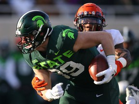 Matt Dotson of the Michigan State Spartans battles for extra yards after a first half catch against Milo Eifler of the Illinois Fighting Illini at Spartan Stadium on November 09, 2019 in East Lansing, Michigan.