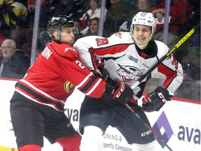 Windsor Spitfires Curtis Douglas, right, is checked by Owen Sound Attack Carter Robinson in OHL action from WFCU Centre Sunday.