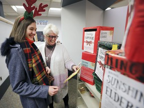 Emily Truman, left, and Kitty Pope, CEO of Windsor Public Library, look over hundreds of handmade Christmas cards at the downtown central branch on Tuesday. The 16-year-old is aiming to collect and distribute 10,000 cards for seniors in Windsor-Essex nursing homes.