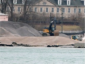 Heavy machinery move tons of crushed stone around the Detroit, Michigan shoreline at Detroit Bulk Storage Wednesday.  Historic Fort Wayne is shown behind.
