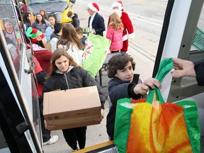 Students and faculty at Christ the King Catholic Elementary School carry gifts to Santa's School Bus on Friday, Dec. 13, 2019, after collecting the donations from their own school along with those from L.A. Desmarais, Notre Dame, St. Andrew, St. Gabriel and St. Joseph's High School. Santa will be making deliveries to local charities such as the Children's Aid Society and Advocating Young Minds.