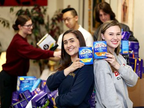 Jada Malott, left, of St. Joseph's Catholic High School and Mira Gillis of F.J. Brennan pose back-to-back during a friendly challenge between Catholic high schools to see which school could donate the most feminine products Tuesday. The official total will be more than 500 products once other schools report their numbers.