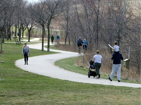 Windsor/Essex, Ontario. March 29, 2020. Area residents keep their distance while walking and riding on trails at East Riverside's Blue Heron Park Sunday.