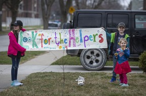 McKinley Nichols, 9, left, Elliot Nichols, 7, and Kate Nichols, 3, take part in a rally for the health-care staff at the Met campus of Windsor Regional Hospital while outside their home on Chilver Road in South Walkerville on March 27, 2020.