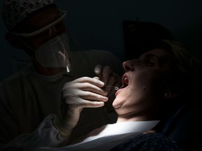 A dentist wearing protective equipment treats a patient in his dental clinic in Guebwiller, eastern France, on May 20, 2020.