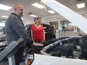 Janis Robert looks over a 2020 GMC Terrain with Claudio Gesuale a salesman at Gus Revenberg Chevrolet Buick GM in Windsor, ON. on Thursday, May 28, 2020. Robert, a frontline health care worker in the city purchased a similar model.
