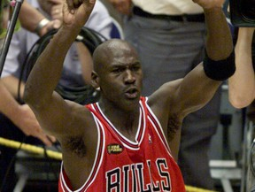 Chicago Bulls Michael Jordan holds up six fingers as he walks around the court after the Bulls defeated the Utah Jazz 87-86 to win the NBA championship in Salt lake City June 14, 1998.