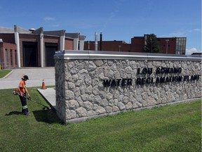 A worker trims the front lawn at the Lou Romano Water Reclamation Plant on Friday, July 31, 2020.