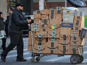 A delivery person pushes a cart full of Amazon boxes in New York City, Feb. 14, 2019.