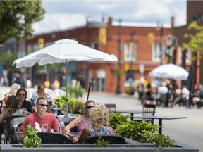People enjoy food and drinks on patios set up on the road on the first day of Kingsville's Open Streets, Saturday, July 11, 2020.