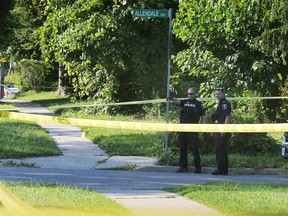 Windsor police officers investigate a blood trail on a sidewalk on Howard Avenue on Aug. 8, 2020.