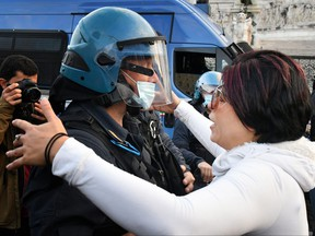 A protester hugs a police officer in provocation on Nov. 15, 2020, in Rome, during a demonstration of anti-mask supporters and against government restrictions over the COVID-19 pandemic, caused by the novel coronavirus.