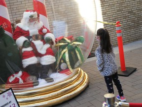 Bella Rivait, age seven, chats with Santa in his snow globe on Maiden Lane in downtown Windsor on Nov. 28, 2020.