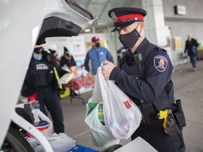 WINDSOR, ONT:. DECEMBER 5, 2020 - Windsor Police Sgt. Andy Drouillard loads donated food items into a police cruiser for the Stuff-a-Cruiser Gift Card and Food Drive outside the Superstore on Dougall Avenue, Saturday, Dec. 6, 2020.  (DAX MELMER/Windsor Star)