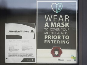 A sign warning people to wear a mask is shown on a door of a Windsor, ON. business on Friday, November 27, 2020. For masks update story.