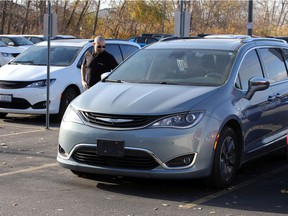 In this Nov. 10, 2020, photo, sales consultant Ryan Eddy walks past a 2017 Chrysler Pacifica Hybrid at Provincial Chrysler.