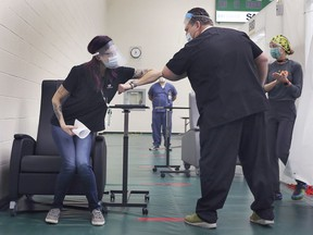 Krystal Meloche, a personal support worker at Seasons Belle River, gets an elbow bump from Windsor Regional Hospital CEO David Musyj on Dec. 22, 2020, after she was the first person in Windsor to receive the COVID-19 vaccine at the St. Clair College SportsPlex.