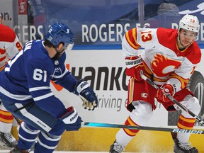 TORONTO, ON - FEBRUARY 22: Johnny Gaudreau #13 of the Calgary Flames skates with the puck against Nic Petan #61 of the Toronto Maple Leafs during an NHL game at Scotiabank Arena on February 22, 2021 in Toronto, Ontario, Canada.