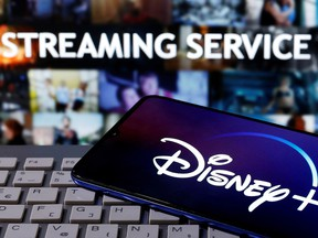 """A smartphone with displayed """"Disney"""" logo is seen on the keyboard in front of displayed """"Streaming service"""" words in this illustration taken March 24, 2020."""