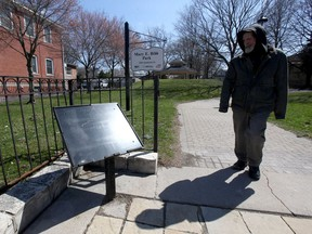 A passerby glances at an empty plaque support at Mary E. Bibb Park, Wednesday March 31, 2021.