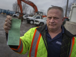 Dale Siefker holds a ticket he received at the Ambassador Bridge for $3,755 while outside his business in Essex on Feb. 28, 2021.