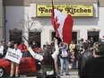A group of demonstrators are shown in front of the Family Kitchen restaurant in Leamington, Ontario on Tuesday, April 6, 2021. The restaurant defied provincial orders and opened for business. The group held a demonstration to support the business owner and protest against lockdown orders.