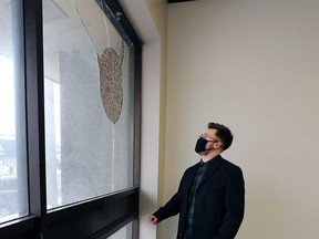 Alexander Reid, executive director of Trans Wellness Ontario (formerly W.E. Trans Support), looks at the damage caused by targeted vandalism at the organization's offices on Tecumseh Road East. Photographed Feb. 22, 2021.
