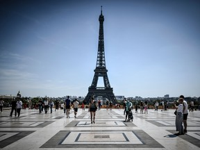 Tourists visit the Esplanade des Droits de l'Homme with the Eiffel Tower in the background, in Paris on August 6, 2020.