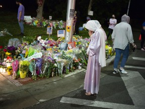 Members of the Muslim community and supporters light candles and place flowers at a memorial on June 8, 2021 in London. A vigil was held earlier in the day, following a vehicular terror attack that left four members of a local Muslim family dead and a nine-year-old boy clinging to life in a local hospital.