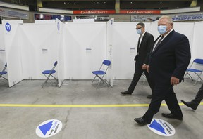 """Ontario Premier Doug Ford, right, tours the """"Hockey Hub"""" mass vaccination centre, known as the CAA Centre, during the COVID-19 pandemic in Brampton on Thursday, June 3, 2021."""
