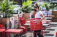 Virginia McIntosh co-owner of Breakwall BBQ, brings out the chairs in preparation for patio reopenings in Toronto.