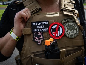 """An attendee wears a """"Three Percenter"""" patch during a Proud Boys rally at Delta Park in Portland, Oregon on September 26, 2020."""