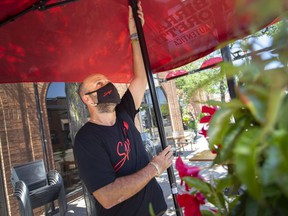 Chris Menard, a server at Spago trattoria and pizzeria on Erie Street East in Windsor, sets up an umbrella in preparation for patio dining on June 10, 2021.