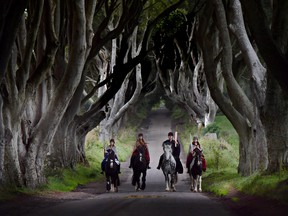 Four actors on horseback dressed in Game of Thrones related costumes carry the Queen's Baton as they make their way way along the Dark Hedges on August 29, 2017 in Antrim, Northern Ireland.