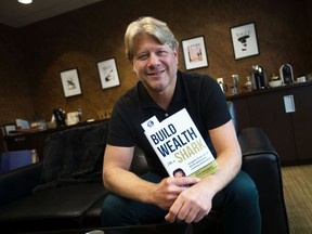 Peter Dobrich of Private Financial Group Inc. in Windsor shows off a copy of Build Wealth Like a Shark in his office on Monday, July 12, 2021. The new book he authored part of is on Amazon's bestseller list in the Financial Investment category.